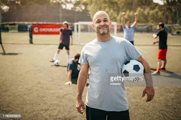 コートにサッカーボールを持つミッドアダルトヒスパニックの男 - ヘアロス ストックフォトと画像