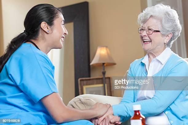Mid adult Hispanic nurse comforts a senior patient