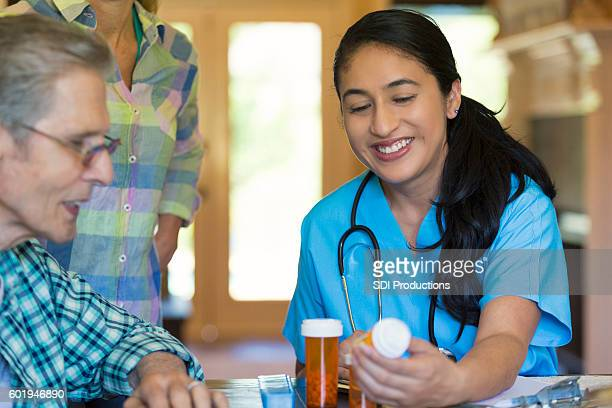 Mid adult Hispanic nurse visits with senior male patient