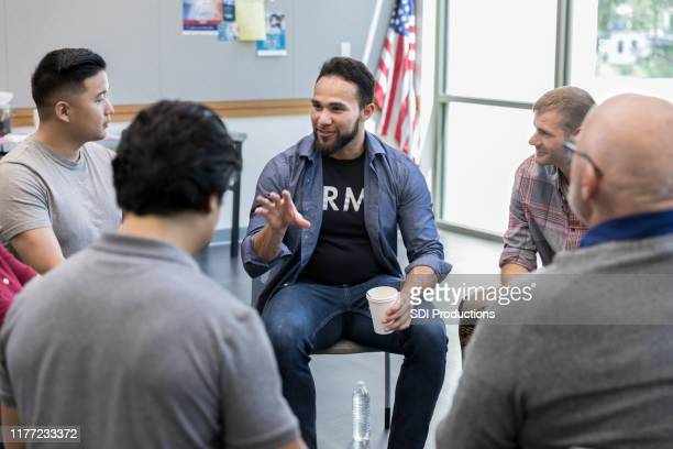 mid adult hispanic veteran talks with fellow veterans - group therapy stock pictures, royalty-free photos & images