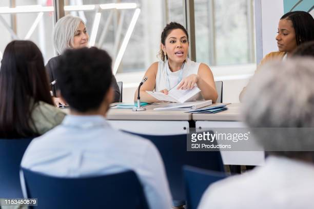 mid adult hispanic woman explains that day's expo schedule - local government building stock pictures, royalty-free photos & images