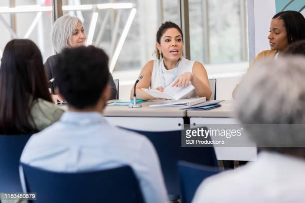 ミッドアダルトヒスパニック女性は、その日のエキスポのスケジュールを説明します - 地方庁舎 ストックフォトと画像