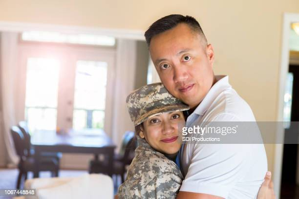 mid adult husband hugs his military wife - military spouse stock pictures, royalty-free photos & images