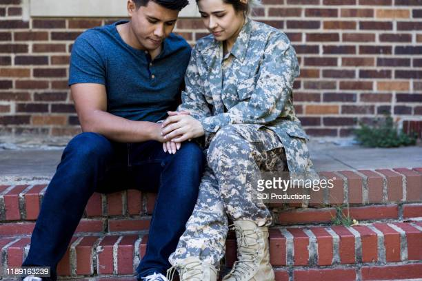 mid adult husband prays with soldier wife before deployment - military praying stock pictures, royalty-free photos & images