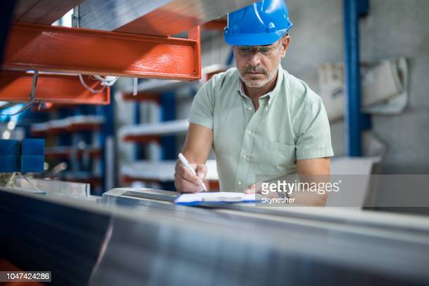 Mid adult inspector taking notes in a steel mill.