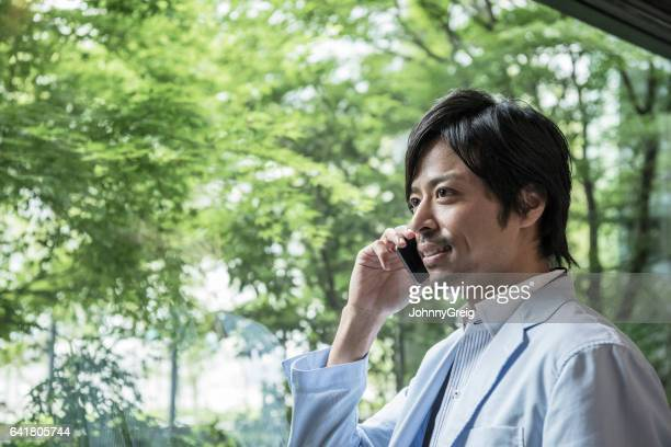 Mid adult Japanese businessman on cell phone with trees