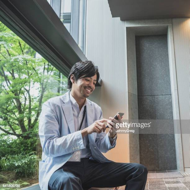 半ば大人の日本のビジネスマンのテキストがメッセージの携帯電話