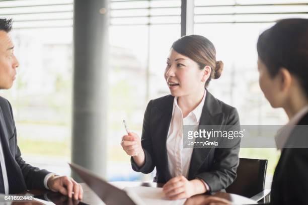 笑顔の同僚に話して半ば成人日本人実業家