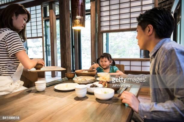半ば成人日本人夫婦の娘と一緒に夕食を食べて - ダイニングテーブル ストックフォトと画像