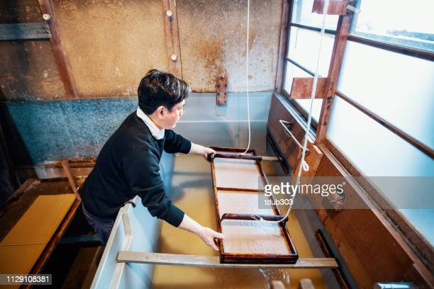 従来の方法を用いた紙を作る大人の日本人男性の中期 - 美術工芸 ストックフォトと画像