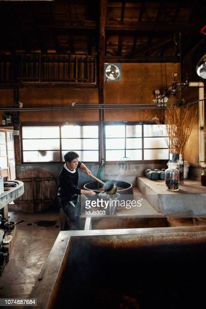 mid adult japanese man preparing the dye to make handmade paper - craft product stock pictures, royalty-free photos & images