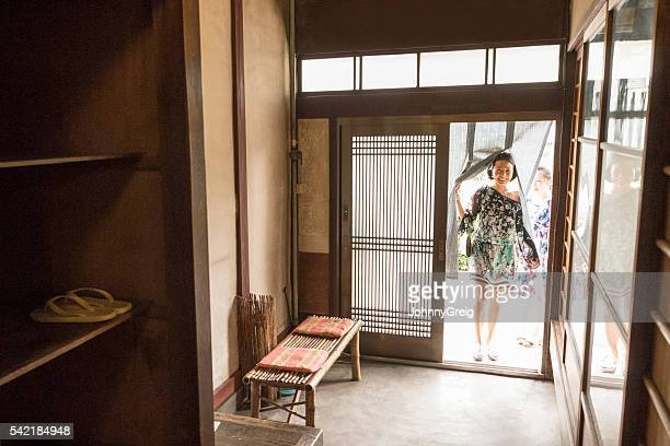 Mid adult Japanese woman entering restaurant