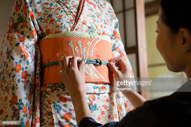 mid adult japanese woman helping young woman into kimono - obi sash stock pictures, royalty-free photos & images