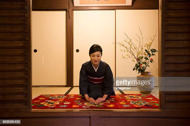 Mid Adult Japanese woman in kimono bowing