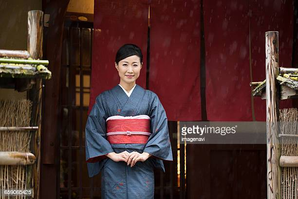 mid adult japanese woman in kimono standing in front of shop - 着物 ストックフォトと画像