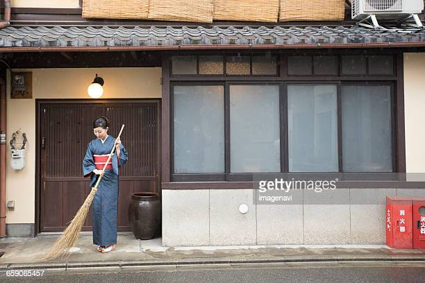 Mid Adult Japanese woman in kimono sweeping with broom