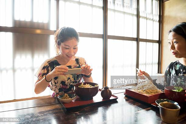 Mid adult Japanese woman taking photo of meal in restaurant