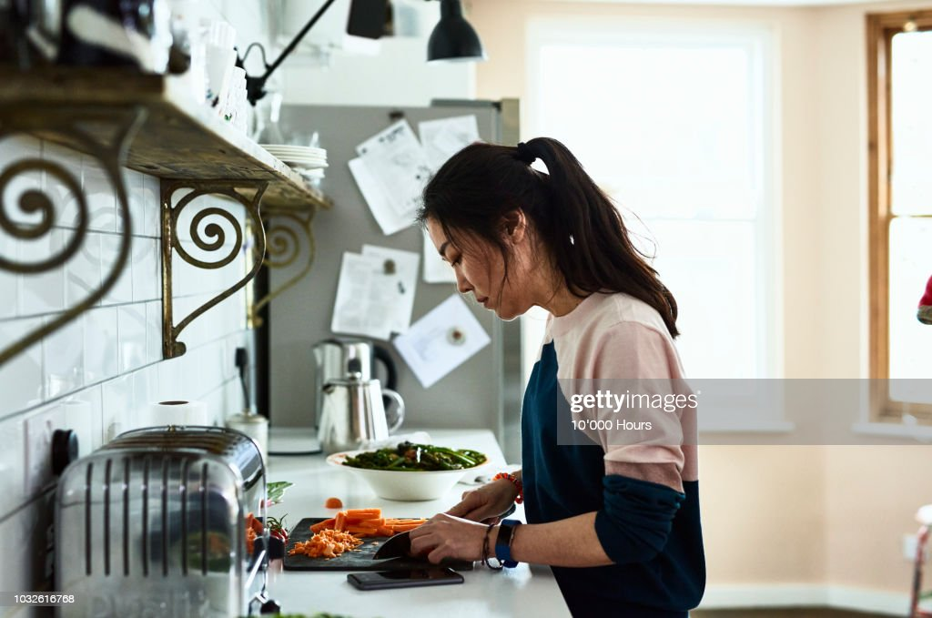 Mid adult Korean woman chopping vegetables on kitchen counter : Stock Photo