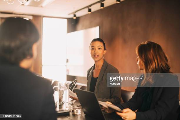 mid adult lawyer sharing ideas with coworkers in meeting at board room - legal system stock pictures, royalty-free photos & images