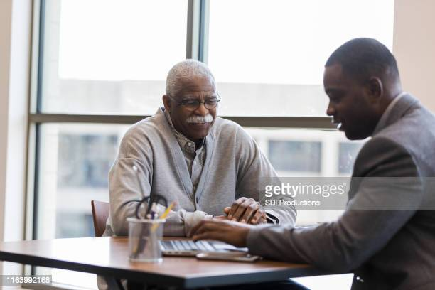 mid adult loan officer helps senior man find best investment - bank customer stock pictures, royalty-free photos & images