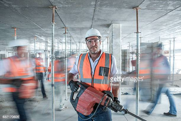 mid adult male builder holding building equipment on busy construction site - bauarbeiter stock-fotos und bilder