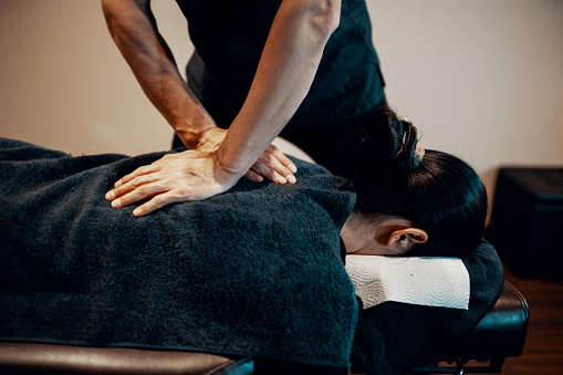 Mid adult male chiropractor treating a female patient 1139374791