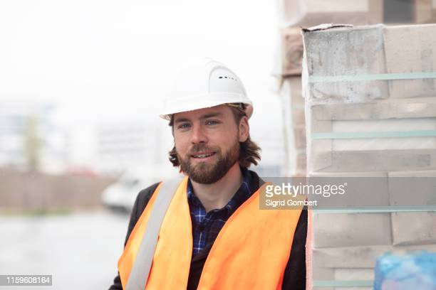 mid adult male civil engineer leaning against stacked building material on construction site, portrait - sigrid gombert stock-fotos und bilder