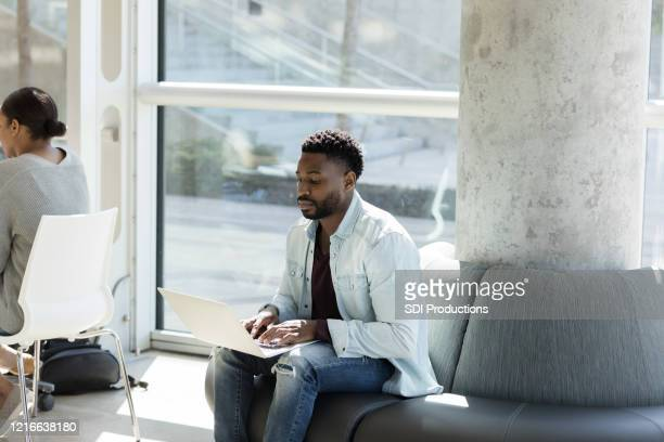 mid adult male college student using laptop - community college stock pictures, royalty-free photos & images