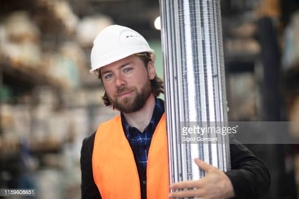 mid adult male construction worker carrying building material on construction site, portrait - sigrid gombert stock pictures, royalty-free photos & images