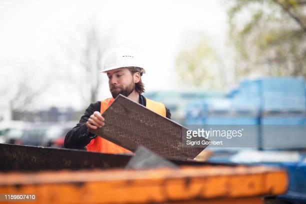mid adult male construction worker putting waste into waste skip - sigrid gombert stock-fotos und bilder