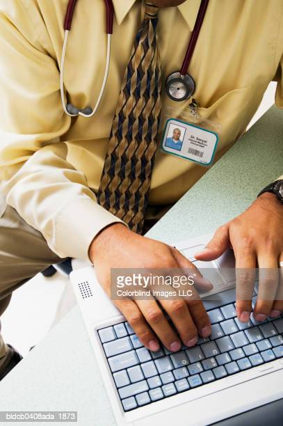 mid adult male doctor working on a laptop - nameplate stock pictures, royalty-free photos & images