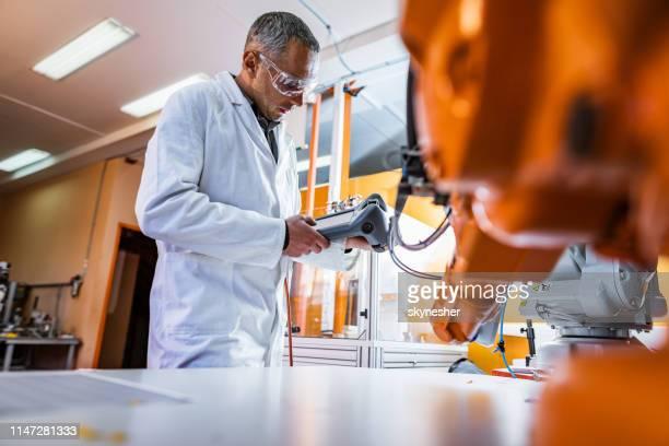 mitteler erwachsener männlicher ingenieur, der in einem forschungslabor am roboterarm arbeitet. - rechnerunterstützte fertigung stock-fotos und bilder