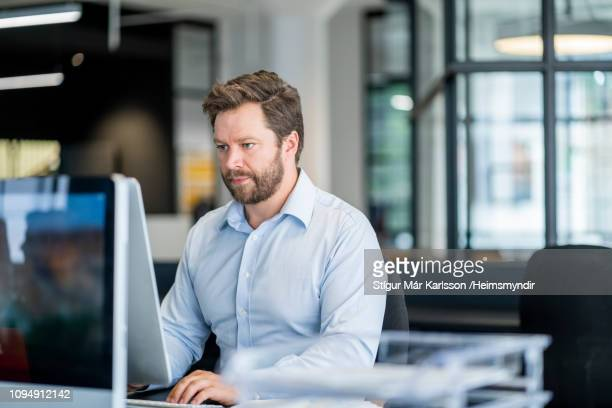 mid adult male entrepreneur using computer at desk - one man only stock pictures, royalty-free photos & images
