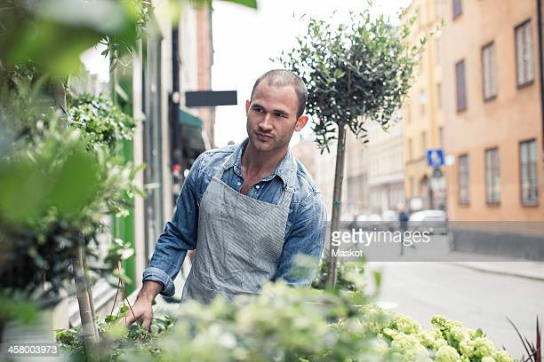 Mid adult male florist working outside flower shop