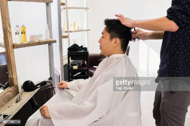 半ば成人男性の脱毛サロン オーナーが若い男性の髪をカットします。