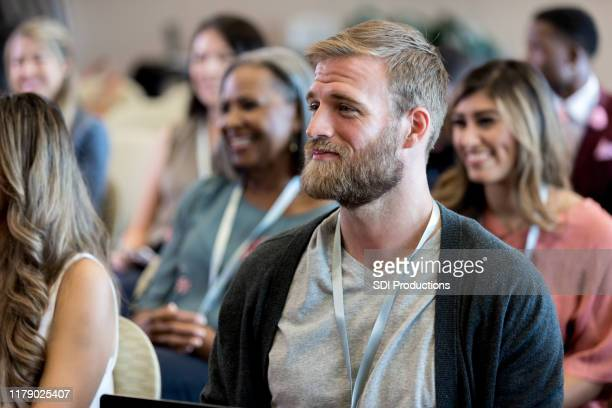 mid adult male hipster listens to unseen conference speaker - attending stock pictures, royalty-free photos & images