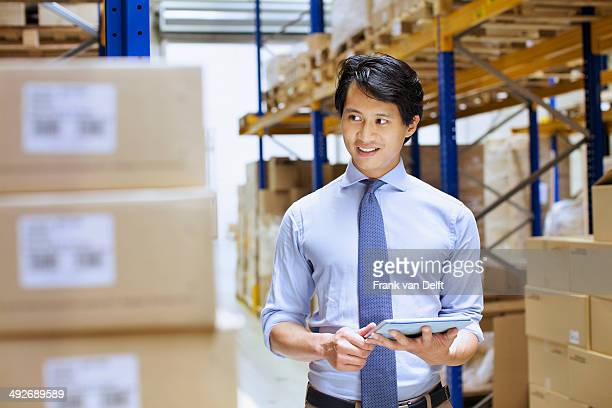 Mid adult male manager using digital tablet in distribution warehouse