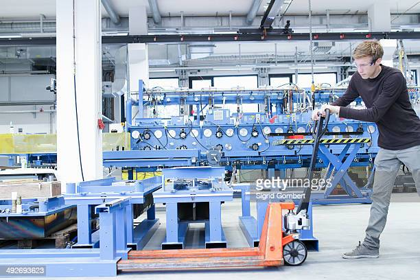Mid adult male moving products on pallet jack in engineering plant