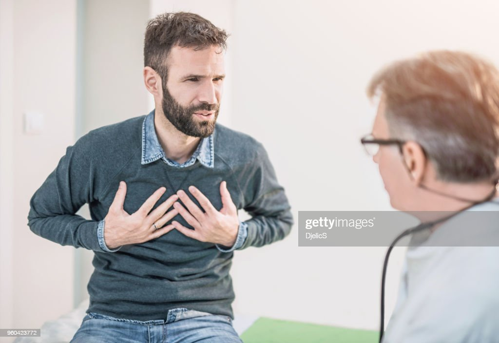 Mid adult male patient describing a chest pain to his doctor. : Stock Photo