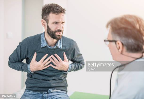 mid adult male patient describing a chest pain to his doctor. - problems stock pictures, royalty-free photos & images