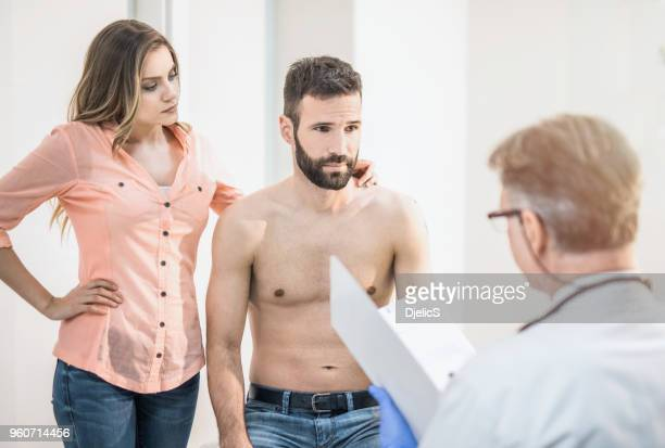 mid adult male patient visiting a doctor with his wife. - mid adult men foto e immagini stock