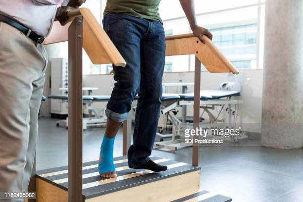 mid adult male puts weight on injured foot; doctor watches - outpatient care stock pictures, royalty-free photos & images