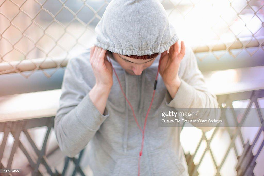Mid adult male runner adjusting earphones : Foto de stock