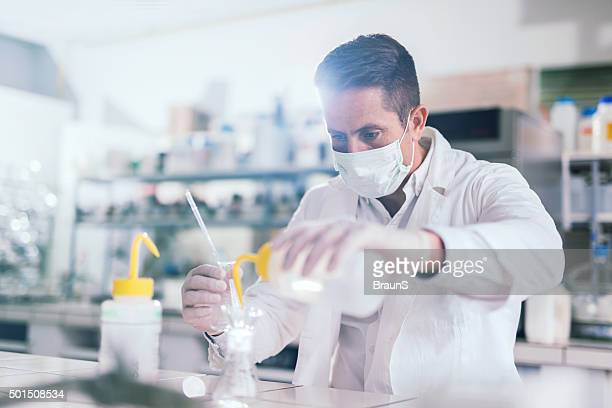 Mid adult male scientist mixing chemical substances for medical research.