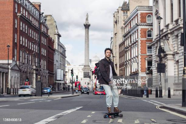 mid adult male skateboarder commuting in central london - city life stock pictures, royalty-free photos & images