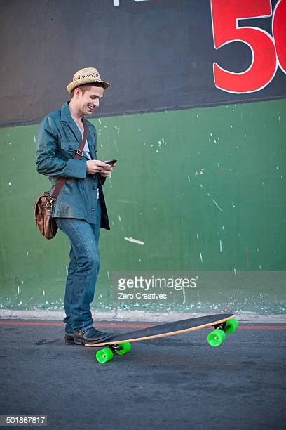 Mid adult male skateboarder reading text message on smartphone