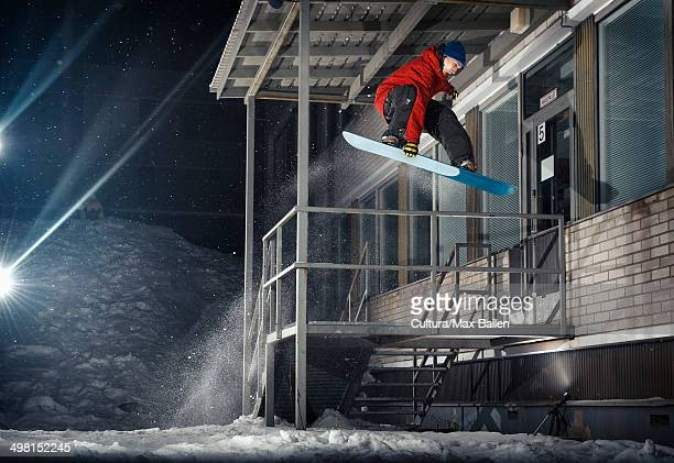 Mid adult male snowboarder jumping mid air from building at night