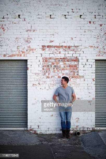 mid adult male standing against a brick white washed wall looking sideways - whitewashed stock pictures, royalty-free photos & images