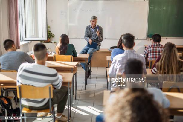 mid adult male teacher giving a lecture to his students in the classroom. - high school building stock pictures, royalty-free photos & images
