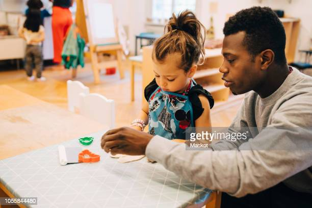 mid adult male teacher playing with girl at table in child care classroom - 保育 ストックフォトと画像